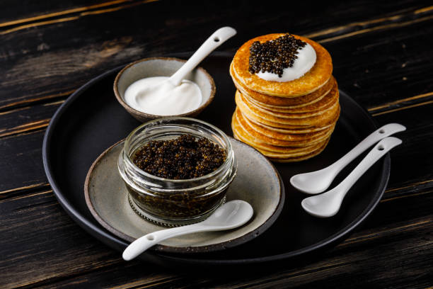black caviar, mini pancakes y sour cream aperitivo festivo en el fondo oscuro - caviar fotografías e imágenes de stock