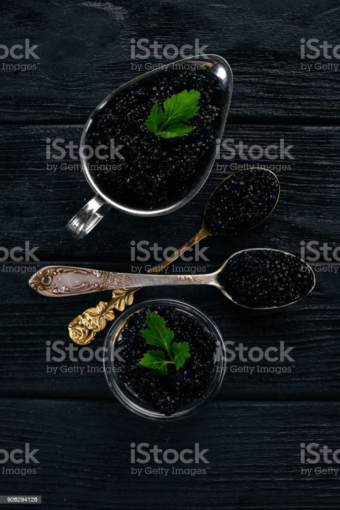 Black caviar. Sturgeon caviar. On a wooden background. Top view. Free space for text. stock photo