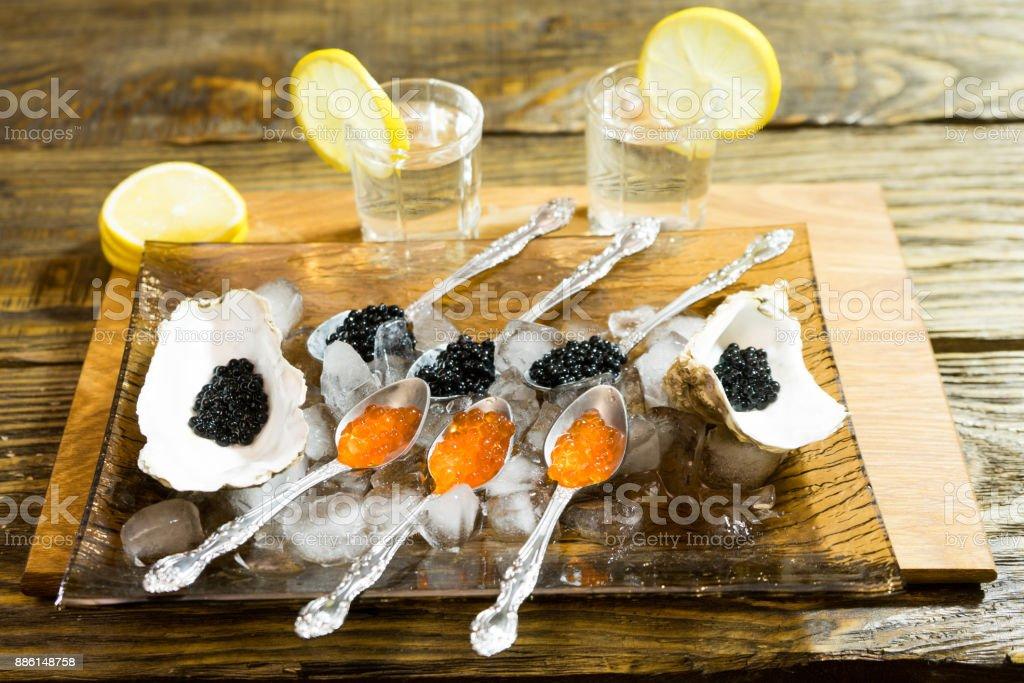 caviar noir aux huîtres et la cuillère sur la glace, à côté de deux tasses de vodka. - Photo