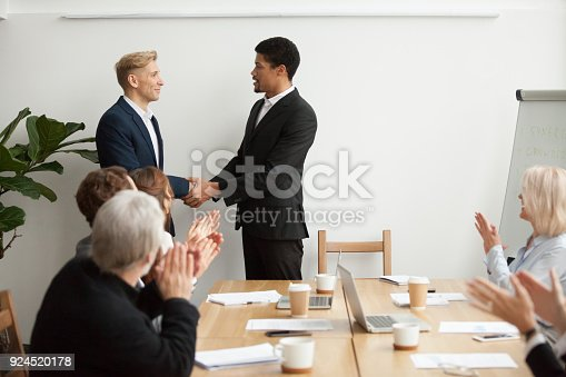 istock Black ceo and white businessman shaking hands at group meeting 924520178