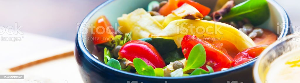 Black ceramic bowl with healthy colorful organic fresh salad stock photo