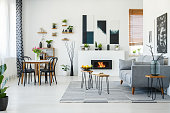 Black chairs at dining table in bright living room interior with grey sofa near fireplace. Real photo