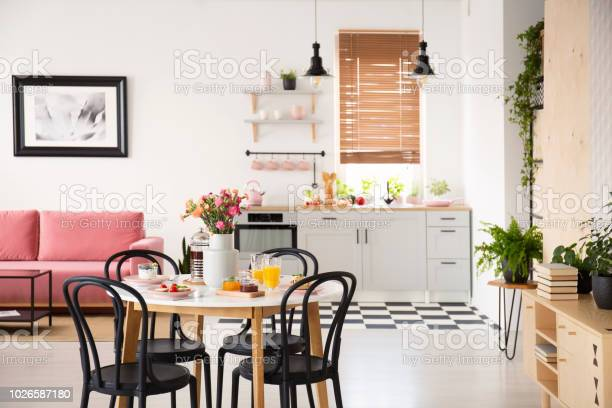 Black chairs at dining table in open space interior with poster above picture id1026587180?b=1&k=6&m=1026587180&s=612x612&h=g9yi750dbffh1a3cxxoy2h bv1rvssaxjywb7o1qqpy=