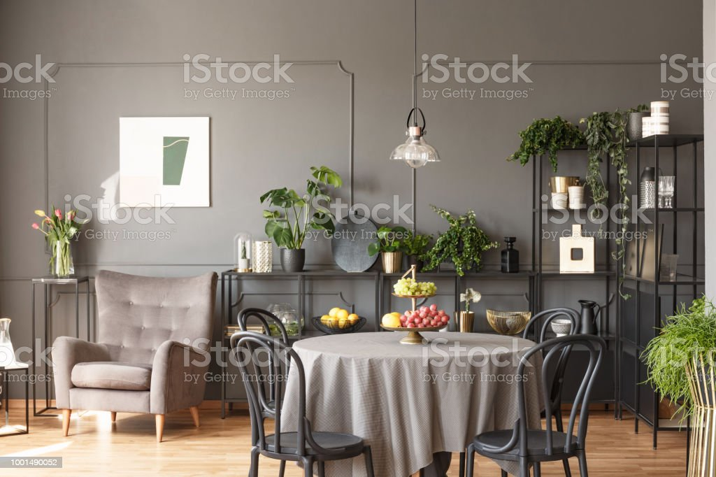Black chairs at round table with fruits in grey loft interior with armchair next to flowers. Real photo stock photo
