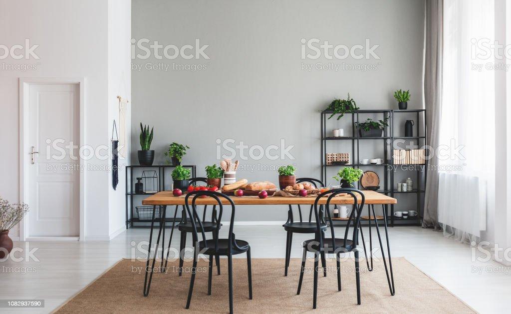 Schwarzen Stuhlen Am Holztisch Mit Essen In Grau Esszimmer Interieur Mit Weissen Tur Echtes Foto Stockfoto Und Mehr Bilder Von Biologie Istock