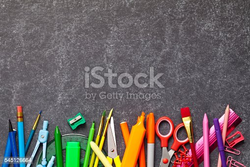 Black chalkboard with some school supplies coming from the bottom border of the frame. The composition includes from left to right: paper clips, crayons, pencil sharpener, scissors, compass, ruler, calculator and pushpins. High angle view DSRL studio photo taken with Canon EOS 5D Mk II and Canon EF 100mm f/2.8L Macro IS USM