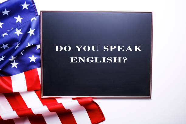 Black chalkboard with the question do you speak English? written in it and the flag of the United States of America. Close up of black chalkboard with the question do you speak English? writen on it, ruffled USA flag and white copy space for text. American English cources concept. United States background, top view. Anglo American stock pictures, royalty-free photos & images