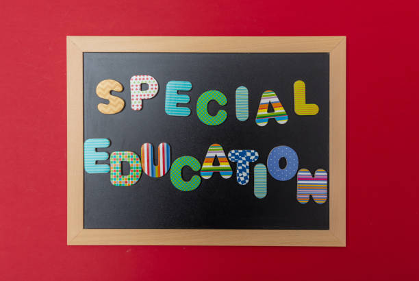Black chalkboard with wooden frame, text special education in colorful letters, red wall background - foto stock