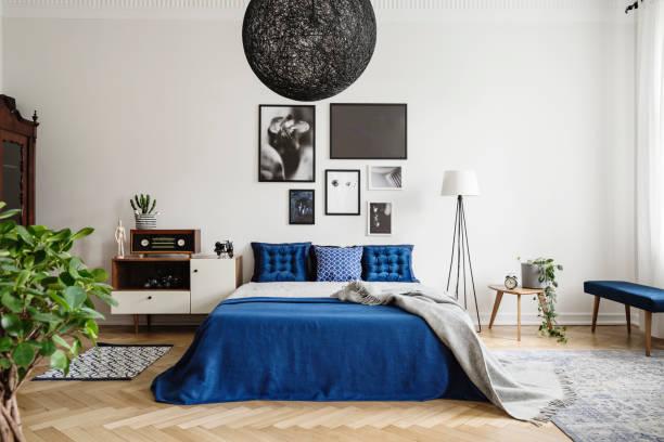 schwarzer kronleuchter in marineblauem schlafzimmer im mietshaus. fußlampe zwischen kingsize-bett und kleinem tisch mit topf und uhr darauf. echtes fotomokomat - schlafzimmer stock-fotos und bilder