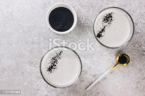 Black charcoal latte on light background. Detox drink. Top view