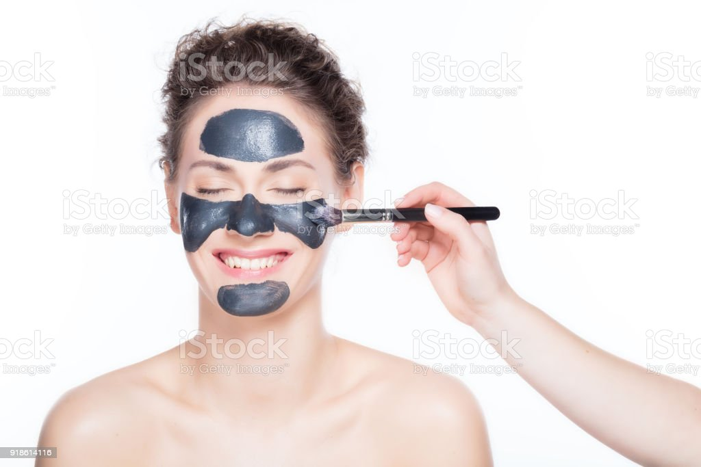 Black charcoal mask application on beautiful woman. stock photo
