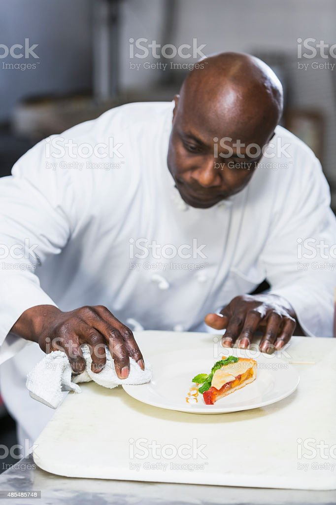 Black chef in a restaurant plating food stock photo