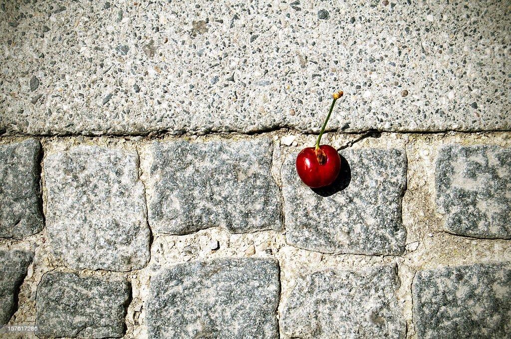 Black Cherry on Concrete Stamped Sidewalk royalty-free stock photo
