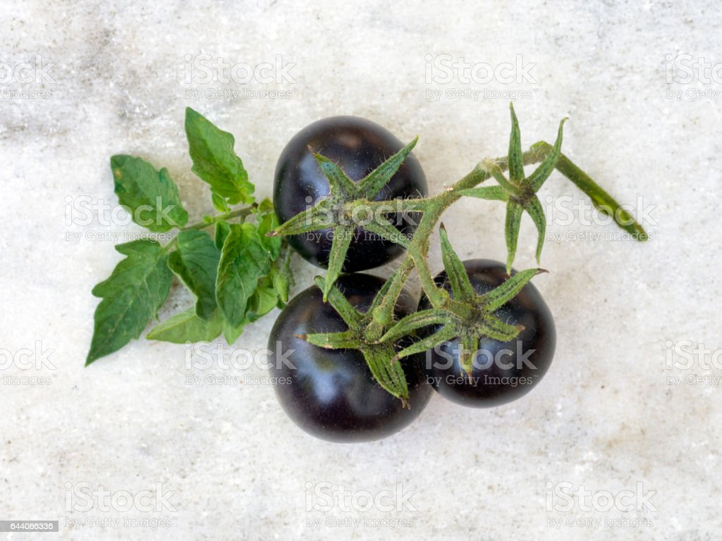 Black cherry tomatoes on pale marble background. stock photo
