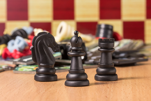 Black Chess Bishop At The Head Of Other Figures On A Blurred Background Of Objects For Table Games Stock Photo - Download Image Now