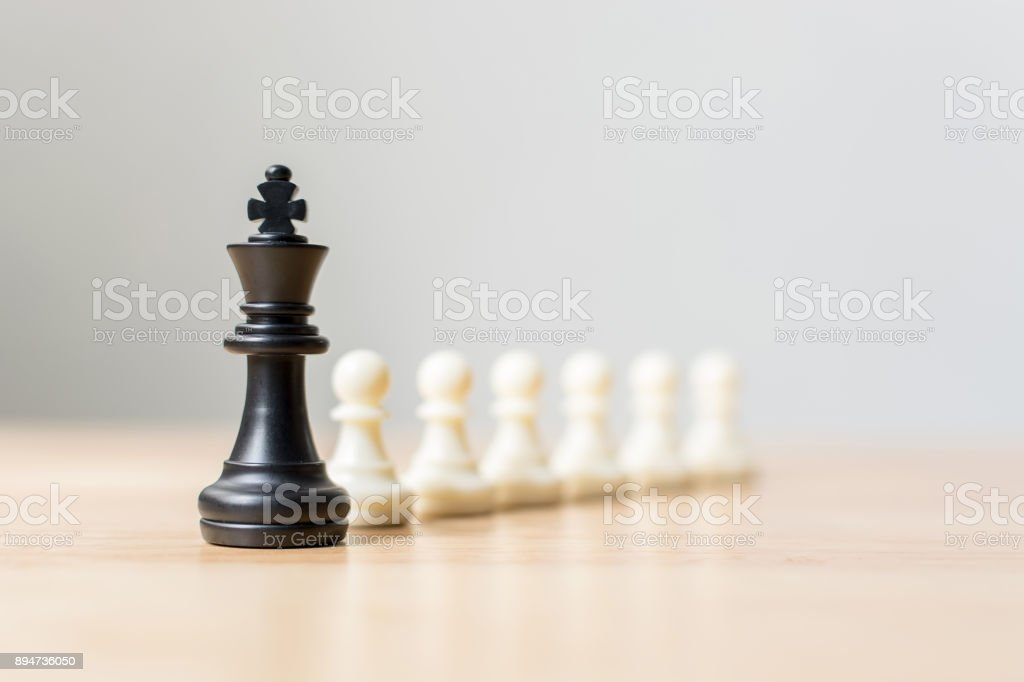Black chess figure leading white chess on wood table, Success of business leader concept stock photo