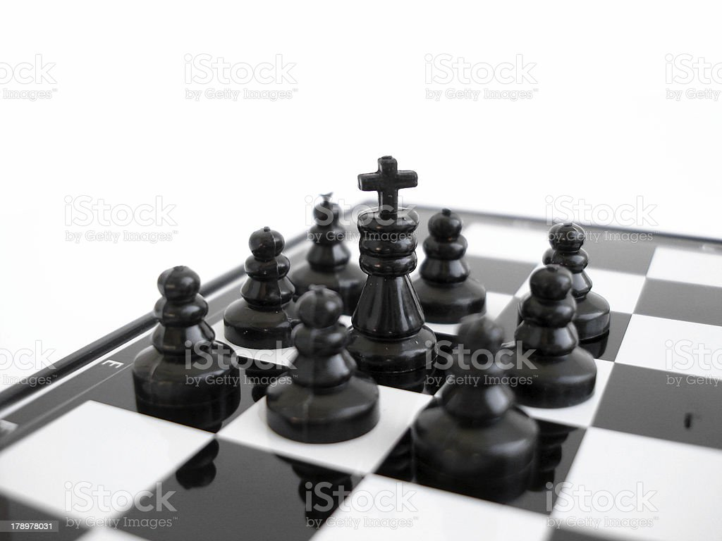 Black chess king stands on a board with figures royalty-free stock photo