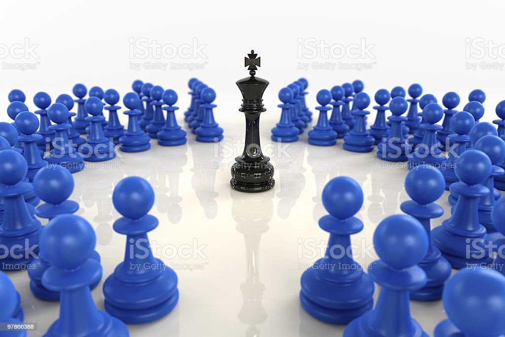 Black chess king surrounded by blue pawns stock photo