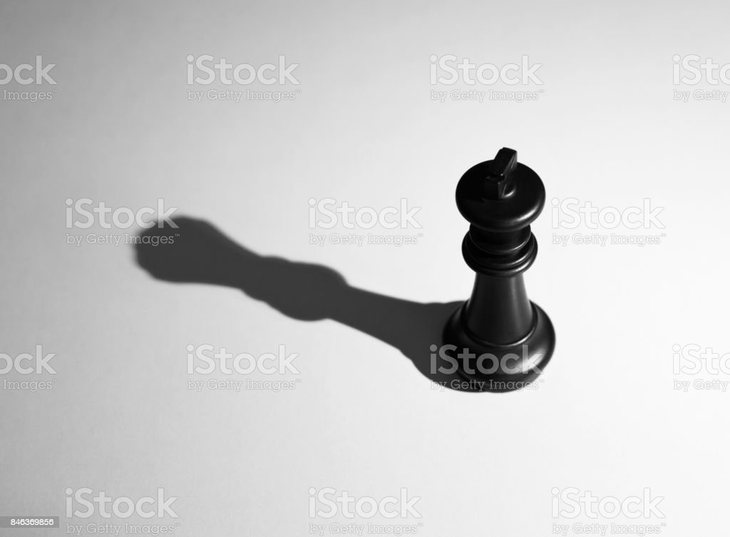 Black chess king with the shadow of a queen stock photo