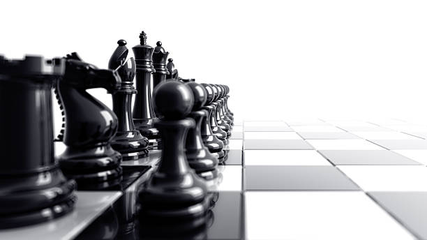 Black chess pieces aligned on the left side of the board stock photo