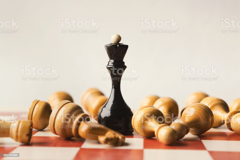 Black chess queen beats whites on chessboard royalty-free stock photo