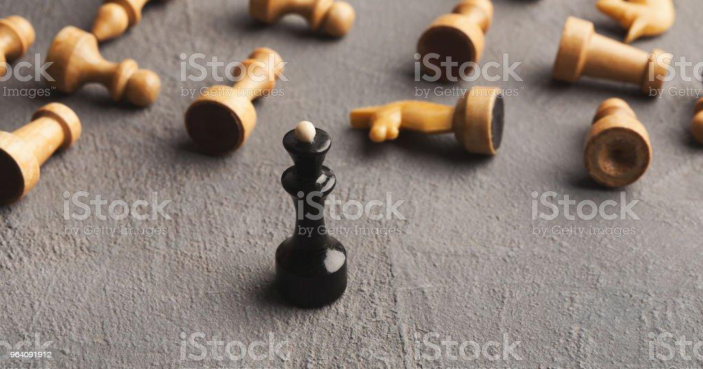 黒チェスのクイーンは、灰色の背景に白人を打つ - もがくのロイヤリティフリーストックフォト