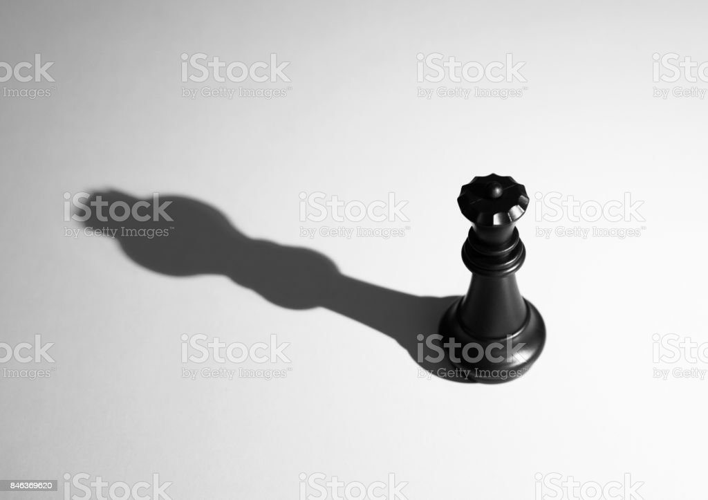 Black chess queen with the shadow of a king stock photo