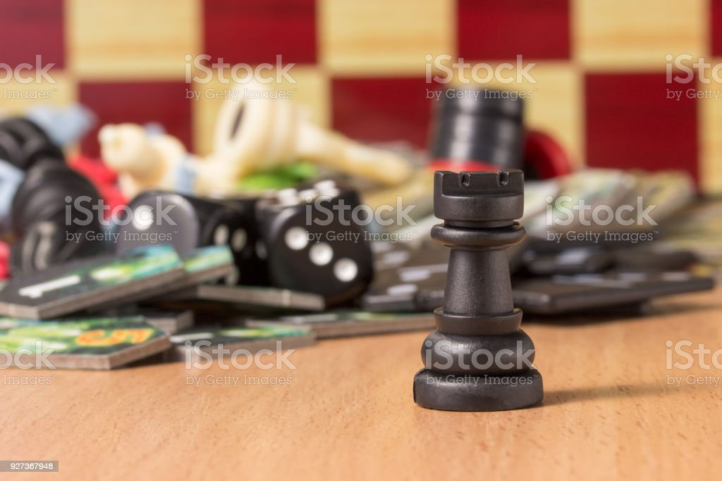 black chess rook on the blurred background of other figures and other objects for table games - Royalty-free Black Color Stock Photo