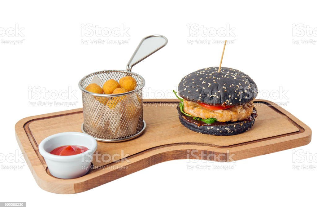 black chicken burger with cheese balls on cutting board isolated on white background zbiór zdjęć royalty-free