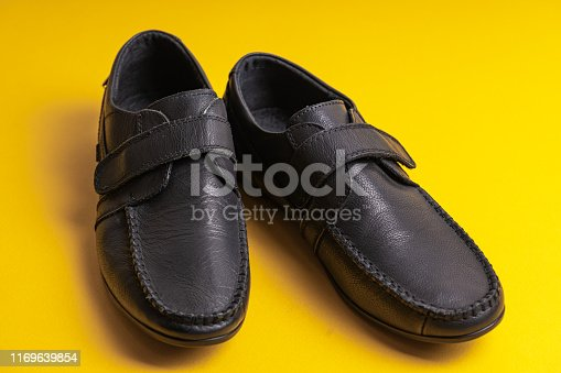Black children's school shoes with Velcro on a yellow background