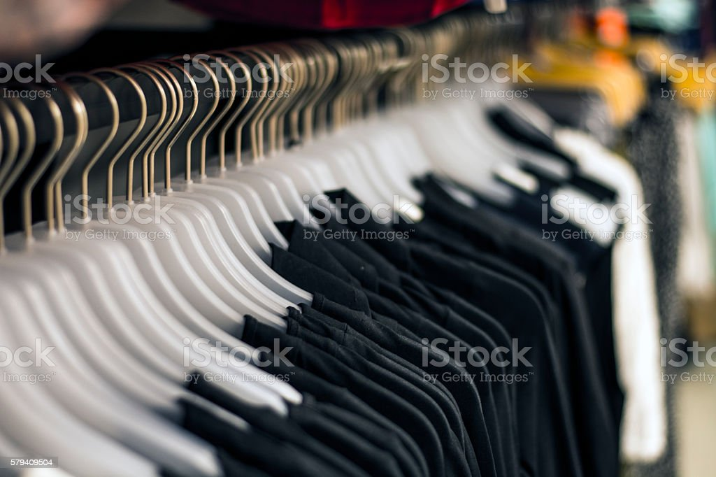 Black chlotes hanging on hangers at the store stock photo