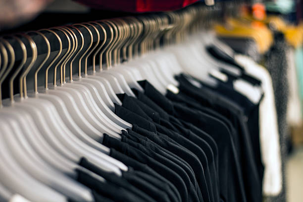Black chlotes hanging on hangers at the store - foto de stock