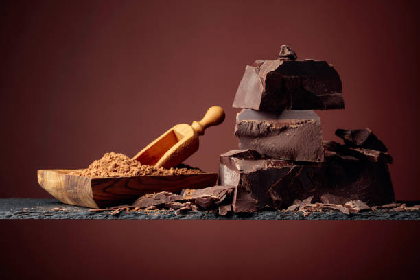 Black chocolate and wooden dish with cocoa powder on a brown background. stock photo