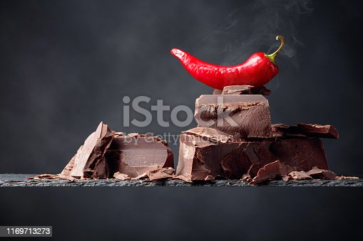 istock Black chocolate with red pepper on a dark background. 1169713273