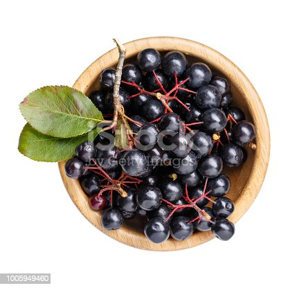 istock Black chokeberry berries ( Aronia melanocarpa ) in wooden bowl isolated on white. Top view. 1005949460