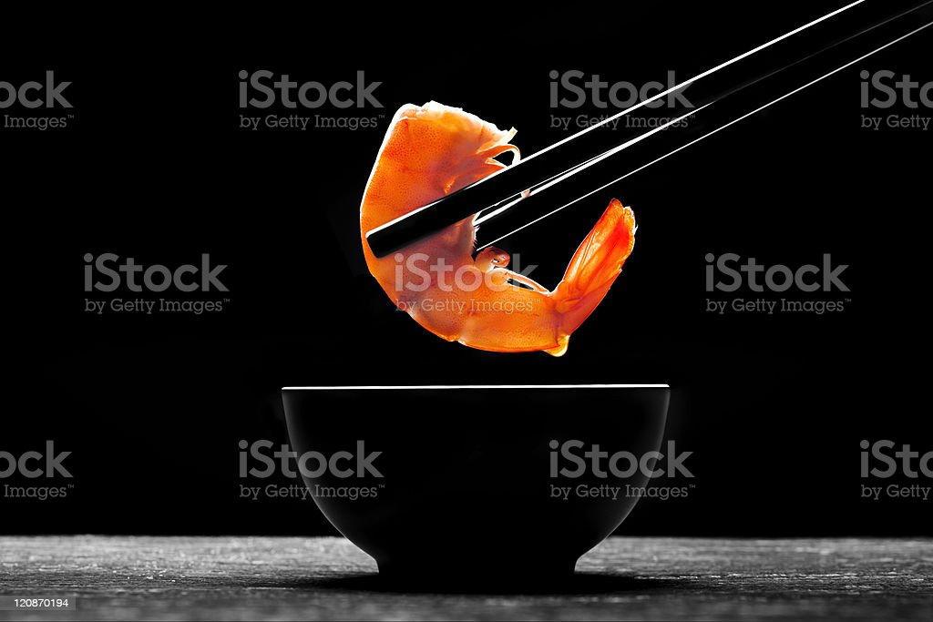 Black chopsticks holding a cooked prawn above a black dish royalty-free stock photo