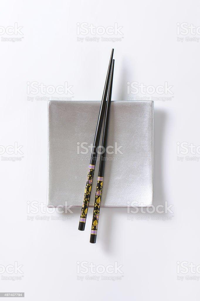 Black chopsticks on empty square plate stock photo