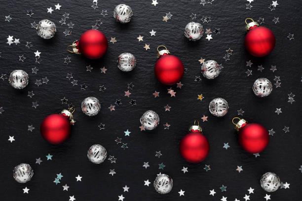 schwarzer Weihnachtshintergrund mit Dekoration, roten und silbernen Kugeln – Foto