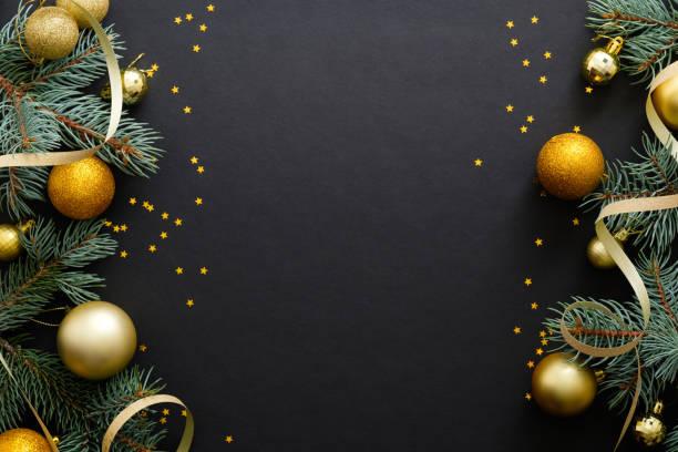 sfondo natalizio nero con decorazioni dorate, palline, rami di abete, coriandoli. festa di natale, inverno, capodanno concept. mockup banner di natale, modello di biglietto d'auguri. - flat lay foto e immagini stock