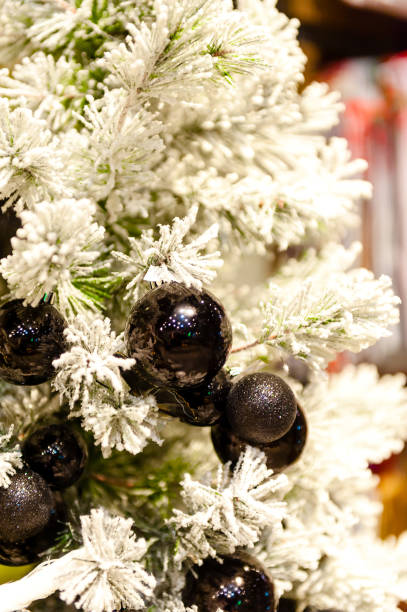 Black christmas ball on the white tree in the background with other decorations and garlands. copy space stock photo