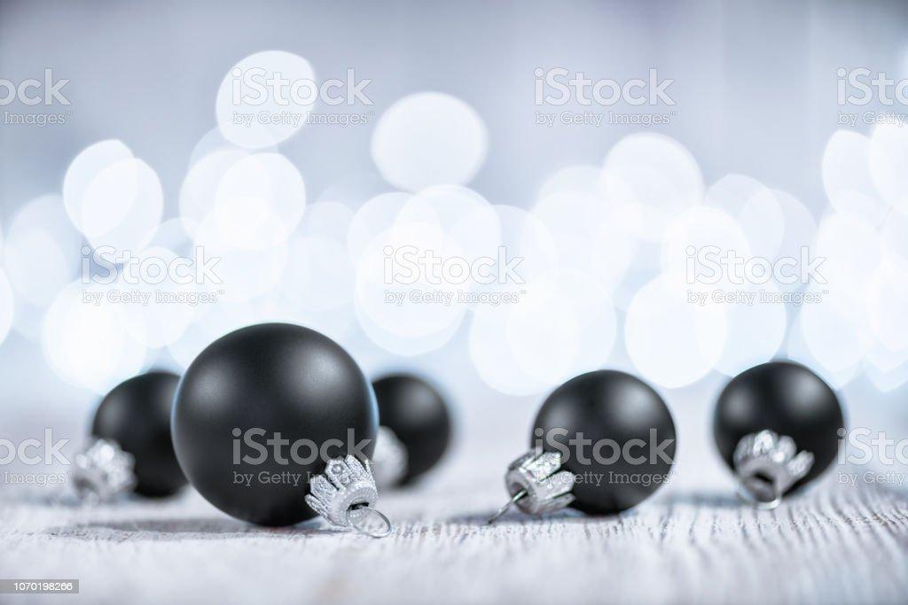 Schwarze Weihnachtskugeln auf weißem Holz und defokussierten Weihnachtsbeleuchtung – Foto