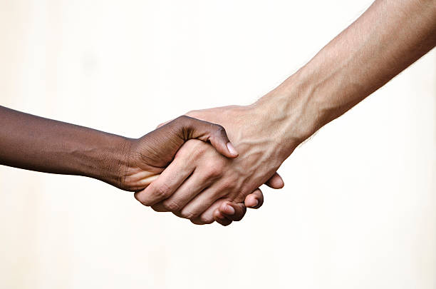 Black Civil Rights Symbol: Multi-Ethnic Handshake Africa Isolated on white, a scene of togetherness and friendship. civil rights stock pictures, royalty-free photos & images