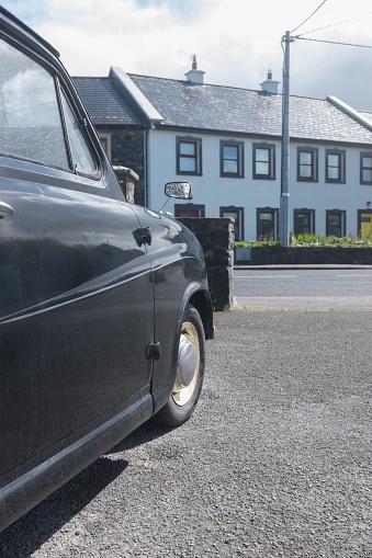 Black classic British car in UK village, vertical