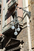 Retro black classic lamppost of wrought iron with three circular lights balloons in Barcelona, Catalonia, Spain