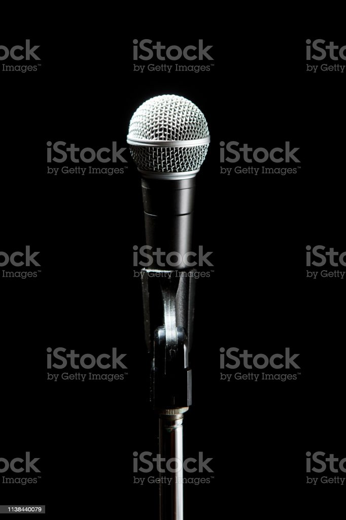 Black classic microphone on black dark background. Music and concert...