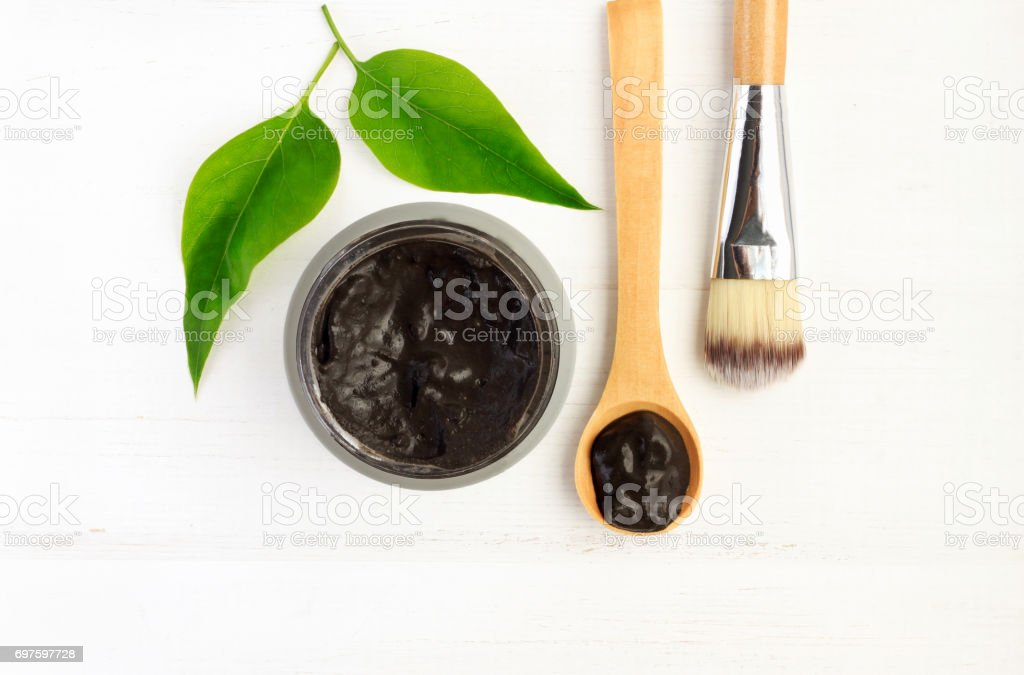 Black clay mineral facial mask, above view stock photo