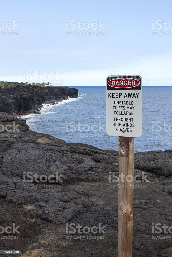 Black Cliffs of Lava with Warning Sign stock photo