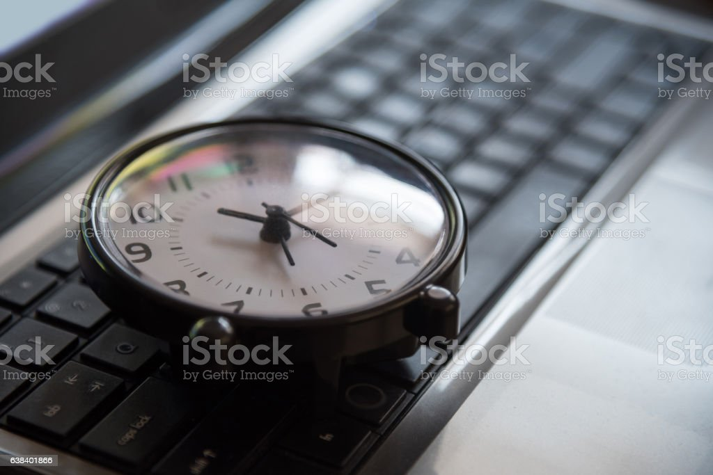 Black clock lay on keyboard time metaphor concept royalty-free stock photo