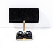 黒のクラッチ バッグと白い背景で隔離のノートブックとサングラス