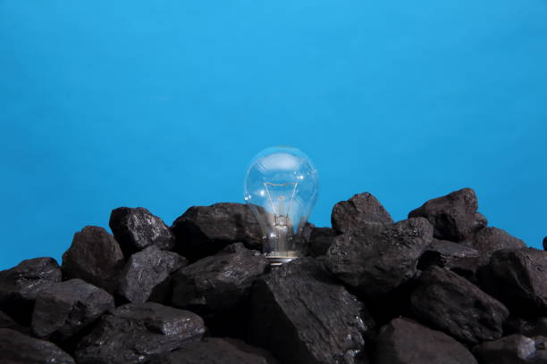 Charbon noir avec une ampoule allumée sur le dessus sur un fond bleu. - Photo